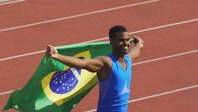 Vlag die van Brazilië in wind, atleet golven die zijn sterkte tonen, winnend de concurrentie stock video