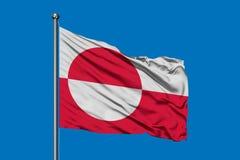 Vlag die van Groenland in de wind tegen diepe blauwe hemel golven stock afbeelding