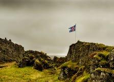 Vlag die van IJsland zich in de wind onder het steenachtige wilde landschap ontwikkelen Stenen met groen mos worden overwoekerd d royalty-vrije stock fotografie
