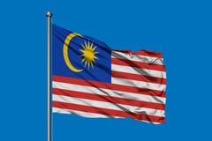 Vlag die van Maleisi? in de wind tegen diepe blauwe hemel golven Maleise vlag stock afbeelding