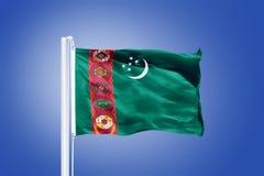 Vlag die van Turkmenistan tegen een blauwe hemel vliegen Royalty-vrije Stock Fotografie