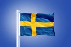 Vlag die van Zweden tegen een blauwe hemel vliegen Stock Foto