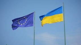 Vlag van de Oekraïne en vlag die van Europese Unie op een achtergrond van een blauwe hemel fladderen stock video
