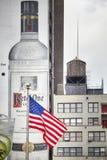 Vlag van de Verenigde Staten van Amerika met Ketel Één van het Wodkabanner en water tank op achtergrond in Manhattan van de binne stock afbeeldingen