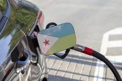 Vlag van Djibouti op de de vullerklep van de auto` s brandstof stock foto