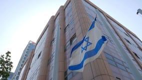 Vlag van Israël met vlaggestok die in wind golven kadetmeisje die de camera en het stellen bekijken stock videobeelden