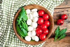 Vlag van Italië van ingrediënten voor vegetarische gezonde salade - kersentomaat, mozarellakaas en arugula op een houten plaat Stock Foto's