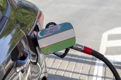 Vlag van Oezbekistan op de de vullerklep van de auto` s brandstof stock foto's