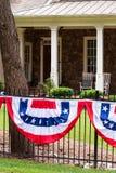Vlaggen die op de omheining door de voorportiek van het huis vliegen stock foto's