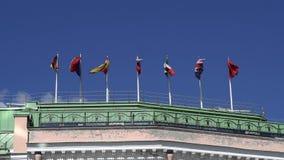 Vlaggen die op een dak van een gebouw in een stad golven stock footage