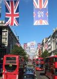 Vlaggen en de rode bussen van Londen in de Straat Londen van Oxford Royalty-vrije Stock Foto's