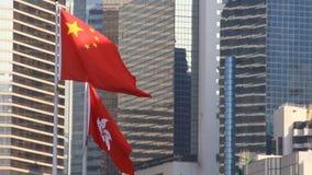Vlaggen van China en Hong Kong die in de wind vliegen stock videobeelden