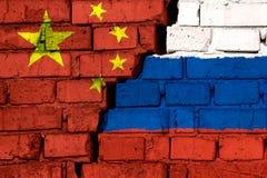 Vlaggen van China en Rusland op de bakstenen muur met grote barst in het midden Symbool van problemen tussen landen royalty-vrije stock fotografie