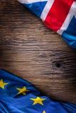Vlaggen van de Europese Unie van het Verenigd Koninkrijk en op rustieke eiken raad het UK en de V.S. markeren samen diagonaal stock foto's