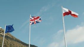Vlaggen van de Europese Unie, de zon van de dagwolken van het Verenigd Koninkrijk en van Gibraltar stock videobeelden