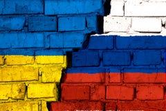 Vlaggen van de Oekraïne en Rusland op de bakstenen muur met grote barst in het midden Symbool van problemen tussen landen royalty-vrije stock foto
