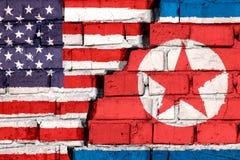 Vlaggen van de V.S. en Noord-Korea op de bakstenen muur met grote barst in het midden Symbool van problemen tussen landen stock foto's
