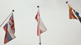 Vlaggen van Europese landen Spanje, Rusland, Zweden, Tsjechische Republiek, Engeland, Zwitserland tegen de hemel stock videobeelden