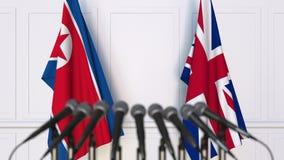 Vlaggen van Noord-Korea en het Verenigd Koninkrijk op internationale bijeenkomst of conferentie het 3d teruggeven Royalty-vrije Stock Afbeelding