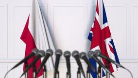Vlaggen van Polen en het Verenigd Koninkrijk op internationale bijeenkomst of conferentie het 3d teruggeven Royalty-vrije Stock Foto's
