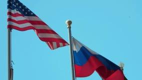 Vlaggen van Rusland en Verenigde Staten op blauwe hemelachtergrond stock footage