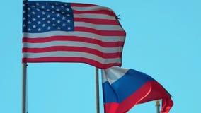 Vlaggen van Rusland en Verenigde Staten op blauwe hemelachtergrond stock videobeelden