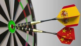 Vlaggen van Spanje en China op pijltjes die bullseye van het doel raken Internationale samenwerking of de concurrentie conceptuel stock foto's
