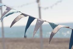 Vlaggenslinger op het overzeese strand Stock Afbeeldingen