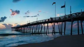 Vlaggenvlieg op een oceaanpijler bij zonsopgang Royalty-vrije Stock Fotografie