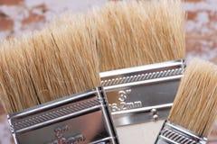 Vlak die Chip Painting Brush op bakstenen muur wordt ge?soleerd stock foto's
