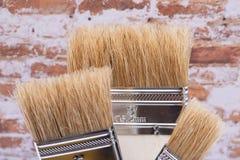 Vlak die Chip Painting Brush op bakstenen muur wordt ge?soleerd stock fotografie