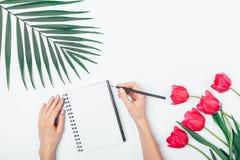 Vlak leg bloemenregeling van de handen van de vrouw het schrijven royalty-vrije stock afbeelding