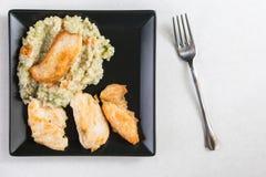 Vlak leg boven gebraden kippen wit vlees met risotto in de zwarte vierkante plaat op het witte marmer Royalty-vrije Stock Foto's