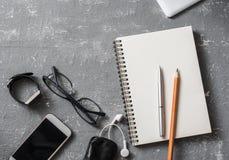 Vlak leg bureauwerkplaats Bedrijfs of onderwijstoebehoren - Blocnote, telefoon, glazen, pennen, potloden, hoofdtelefoons op grijz royalty-vrije stock foto's