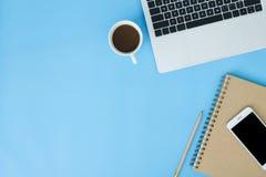 Vlak leg de hoogste foto van het meningsmodel van het werk ruimte met laptop, smartphone, koffie en stationair op blauwe pastelkl royalty-vrije stock foto