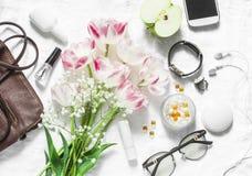 Vlak leg de reeks-lederschool van vrouwen` s toebehoren, tulpenboeket, schoonheidsmiddelen, glazen, telefoon, appel, hoofdtelefoo royalty-vrije stock foto