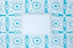 Vlak, leg, een blad van document voor tekst op een blauwe achtergrond met gehaakt wit uitstekend kant, de winterthema, vierkant o stock foto's