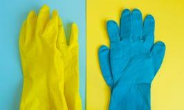 Vlak leg gele en blauwe rubber beschermende handschoenen op dubbele lijstachtergrond voor de lente of dagelijks het schoonmaken H stock foto's