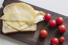 Vlak leg gezond ontbijt met plak van bruin brood, Edammer kaas en tomaten stock afbeelding