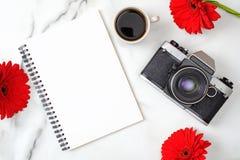Vlak leg het huisbureau van vrouwen De werkruimte met document blocnote, retro fotocamera, koffiekop en madeliefje bloeit op marm royalty-vrije stock fotografie