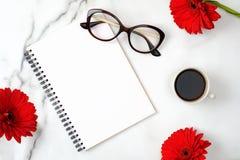 Vlak leg het huisbureau van vrouwen De werkruimte met document blocnote, vrouwelijke glazen, koffiekop en madeliefje bloeit op ma stock fotografie