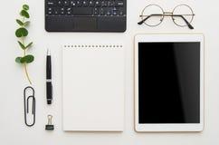 Vlak leg het werkplaats Witte bureaulijst met laptop, klemmen, glazen, notitieboekje en pen Hoogste mening met exemplaarruimte royalty-vrije stock afbeelding