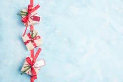 Vlak leg hoogste mening drie vakjes van de Kerstmisgift in ambachtdocument met rode linten op blauwe achtergrond Het concept van  Stock Foto's