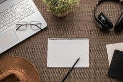 Vlak leg Hoogste mening van een bureau met laptop, notitieboekje, hoed, potlood, hoofdtelefoons, glazen, paspoort, boeken en inst stock afbeelding
