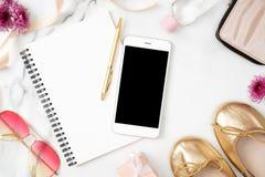 Vlak leg huisbureau Vrouwelijke werkruimte met mobiele telefoon, document blocnote, gouden schoenen en vrouwelijke toebehoren op  royalty-vrije stock foto's