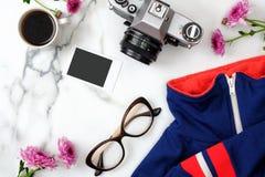 Vlak leg huisbureau Vrouwelijke werkruimte met modieuze kleren, glazen, uitstekende fotocamera, koffiekop en bloemen op marmer royalty-vrije stock afbeeldingen