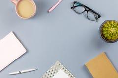 Vlak leg huisbureau Vrouwelijke werkruimte met notaboek, oogglazen, theemok, agenda, installatie De ruimte van het exemplaar Royalty-vrije Stock Foto