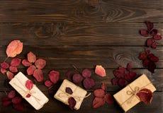 Vlak leg kader van de herfst karmozijnrode bladeren en giftdozen op dark Stock Afbeelding