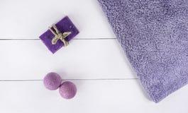 Vlak leg kuuroordbad op witte houten achtergrond, hoogste meningsproducten voor hygiëne Bommen en zeep van lavendel met handdoek stock foto
