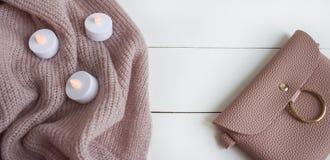 Vlak leg manier op witte houten achtergrond, hoogste menings stoffige roze kleren en toebehoren met kaarsen stock fotografie